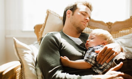 Father and son nap on the sofa