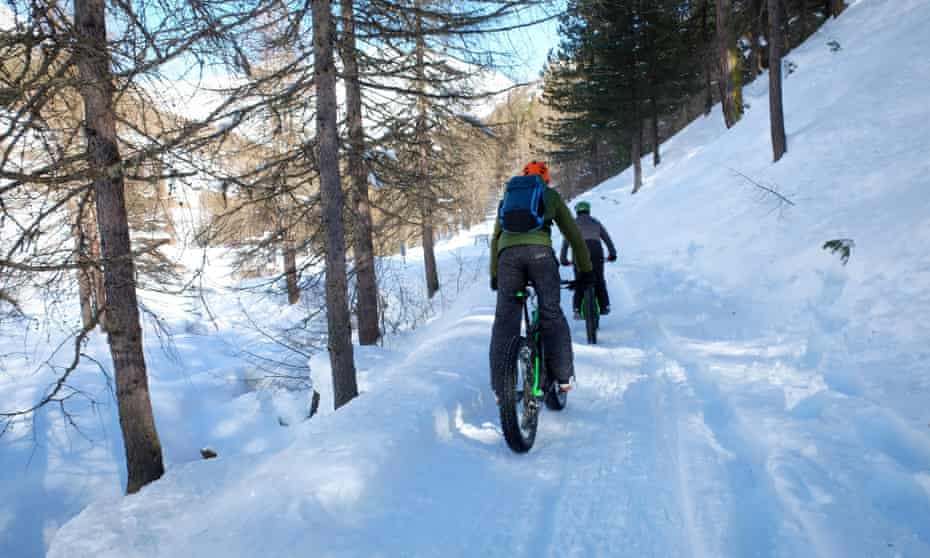 Mountainbiker with Fat Bike on snowy forest road, Val Federia, Livigno