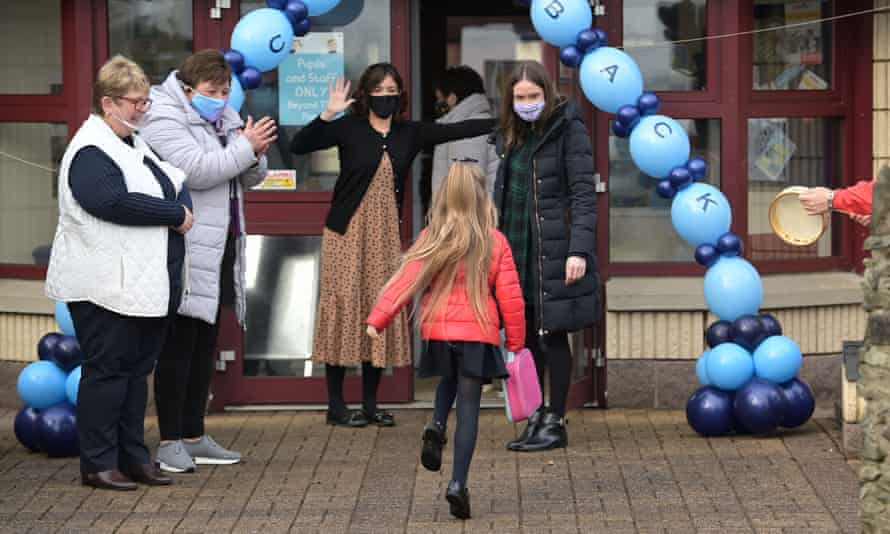 A pupil returning to Hazelwood integrated primary school after lockdown in Newtownabbey, Northern Ireland, 8 March 2021.