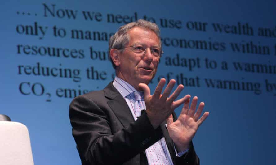 Sir David King giving a presentation on stage ina a shirt and jacket, with a display of highly magnified text on a screen behind him
