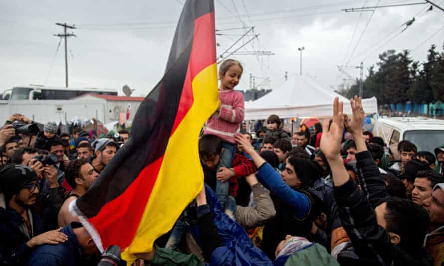 People at Greece's border with Macedonia on Monday wave a German flag.