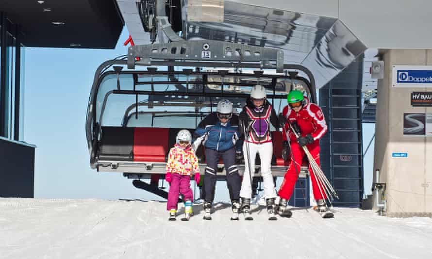 Family skiers at the top of a slope, Fieberbrunn