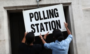 Workers prepare signs outside their polling station on general election day in London
