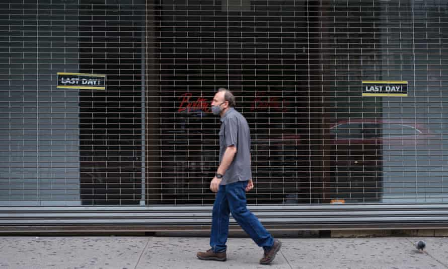 A man walks past a shuttered storefront in New York, New York.