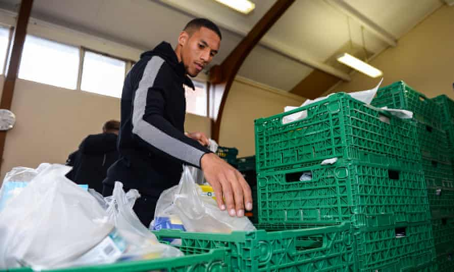 Isaac Hayden of Newcastle United packs food packs during a visit to Newcastle West End Food bank.