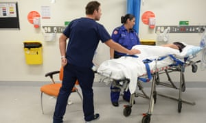 Ambulance and medical staff attend to a patient at St Vincent's hospital emergency department, Sydney.