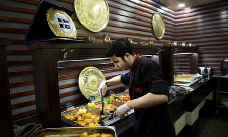 Said Mahmoud adds chicken to the lunch buffet at Jasmin Alsham restaurant