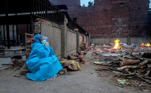 A relative mourns during the last rites of a Covid-19 victim at a makeshift cremation ground in New Delhi, India.