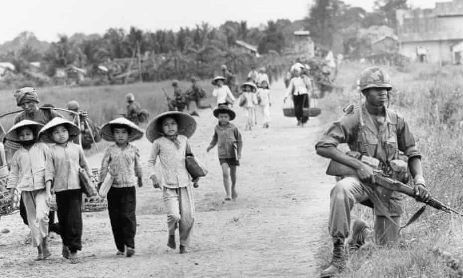 In this December 1965 photo shot by AP photographer Horst Faas, a US 1st Division soldier guards Route 7 as Vietnamese women and school children return home to the village of Xuan Dien from Ben Cat.