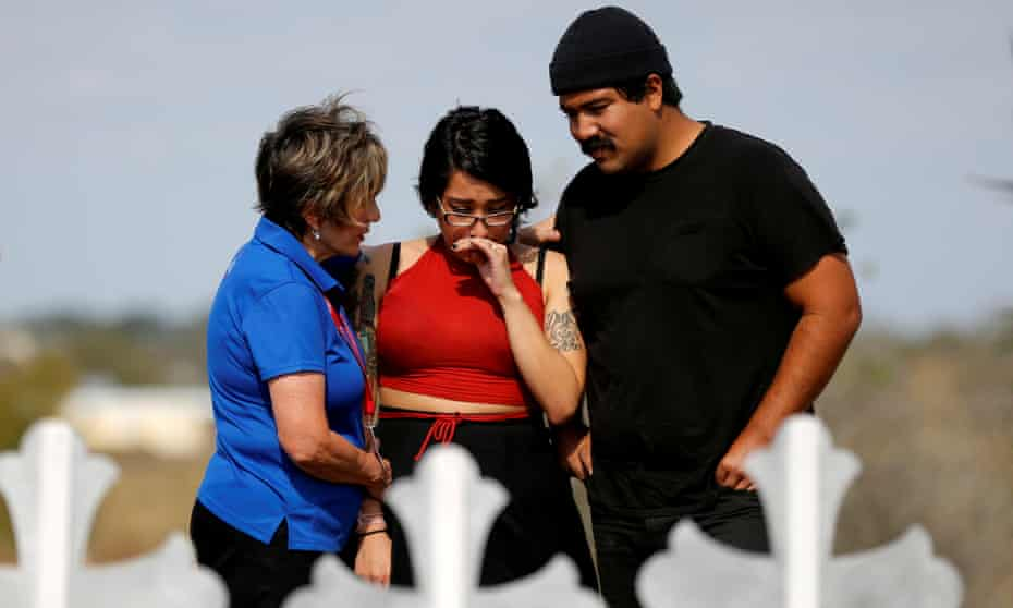 Mourners pray at a memorial in memory of the victims killed in the Texas shooting.