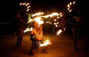 """Burning Man participants from the """"Revolutionary Motion"""" fire conclave spin fire hoops in front of the effigy of """"The Man"""" just before the effigy is burned"""