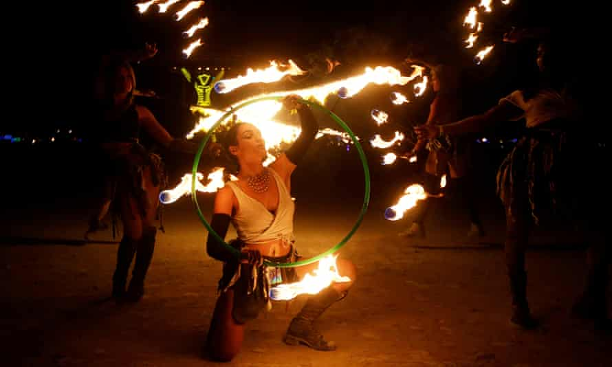 Members of the Revolutionary Motion fire conclave spin fire hoops at Burning Man in 2017.