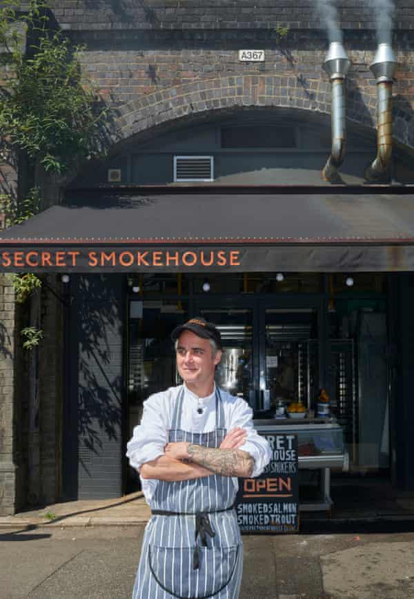 Max Bergius in a striped apron standing outside Secret Smokehouse, built in a railway arch with two steel chimneys and a large awning