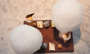 Two large circles of candyfloss on a wooden board with a variety of other smaller desserts