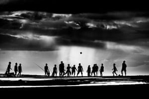 Sunset on Pekutatan beach in Bali and local kids meet to play football before darkness falls.