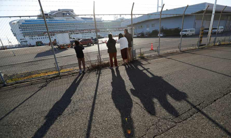 People in Yokohama, Japan, look at the cruise ship Diamond Princess, where dozens of passengers tested positive for coronavirus