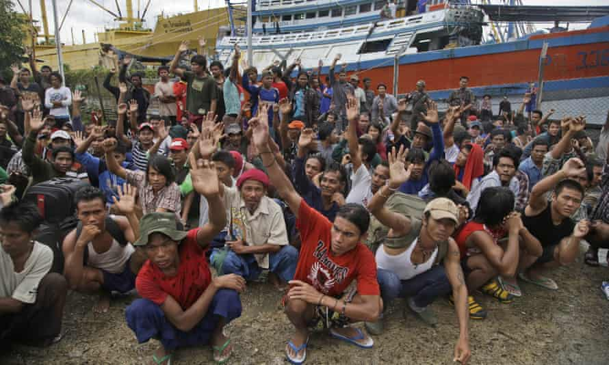 In this April 2015 file photo, Burmese fishermen raise their hands as they are asked who wants to go home at the compound of Pusaka Benjina Resources fishing company in Benjina, Aru Islands, Indonesia.