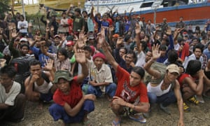 Myanmarese fishermen raise their hands as they are asked who among them wants to go home, at a port in Indonesia, April 2015.