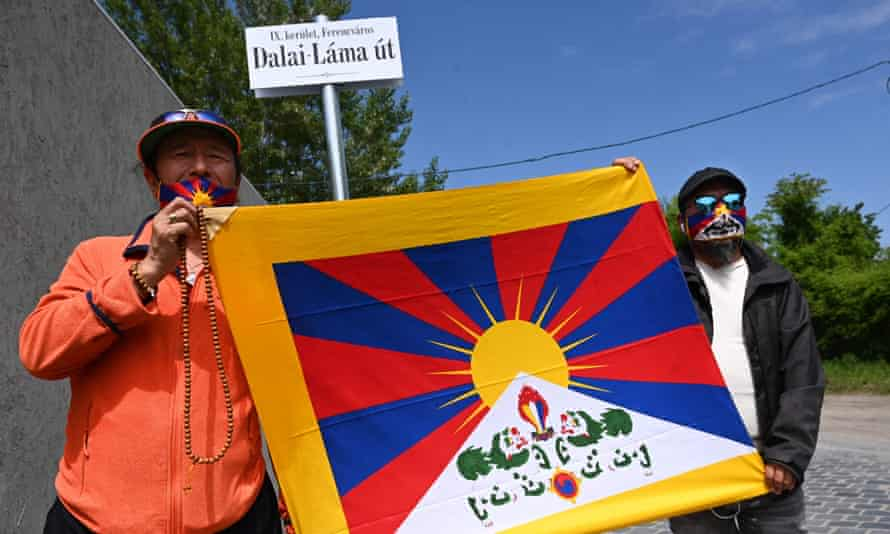 Activists hold the Tibetan flag underneath a street sign reading 'Dalai Lama Road', close to the planned Chinese Fudan university campus in Budapest.
