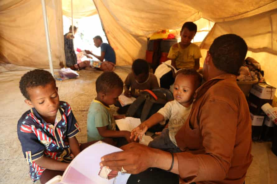 Ahmed Ali Muqbel Ali teaches his children in their tent in Al-Malika camp for displaced people in Taiz, Yemen, after the closure of the schools because of Covid-19.