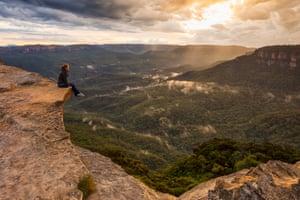 Woman sitting on a mountain ledge, Blue Mountains National Park.