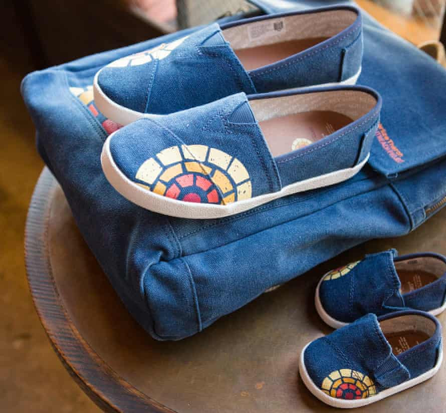 Adult canvas shoes on a canvas bag next to children's shoes