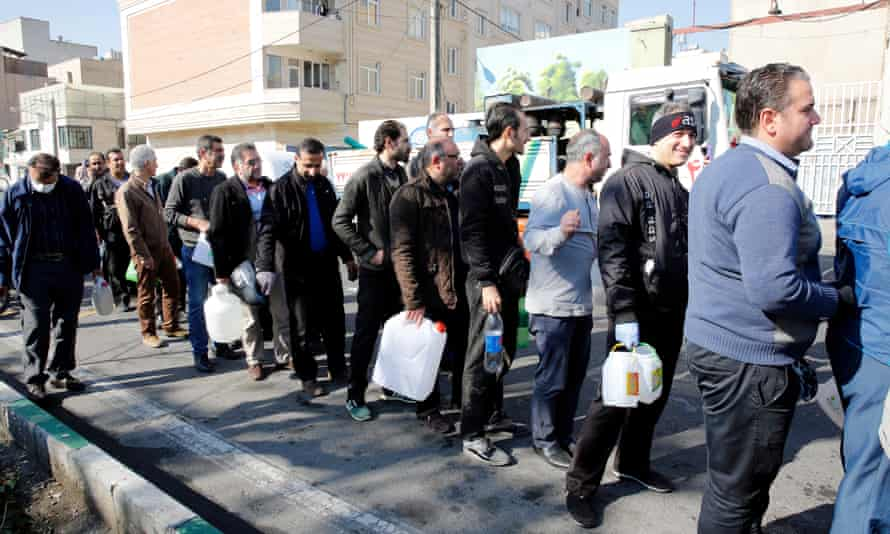 Iranians queue as the Revolutionary Guards give out disinfection liquid in Tehran.