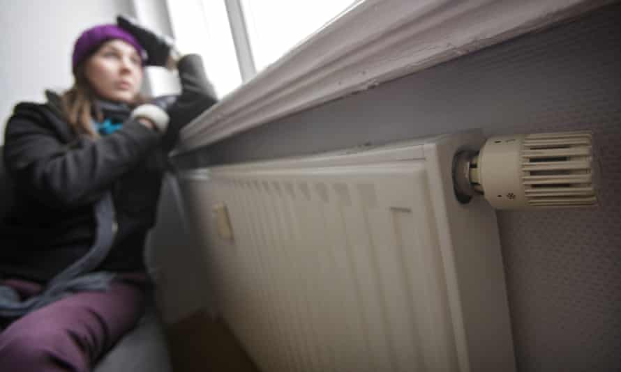 Young woman sitting near a radiator
