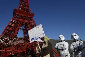 Avaaz activists dressed as Yoda and Star Wars stormtroopers stand in front of a replica of the Eiffel Tower
