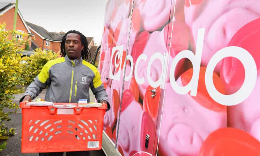 A driver delivers groceries in an Ocado Percy van.