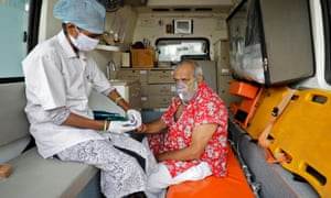 A paramedic uses an oximeter to check the oxygen level of a patient inside an ambulance while waiting to enter a Covid-19 hospital for treatment.