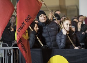 Spectators wave Indigenous flags as they watch Mike Parr make his way down under the road
