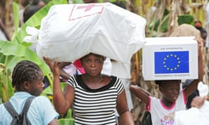 Aid is distributed for victims in Haiti in 2010. The US says it is ending the program because conditions in Haiti have improved, but others called the move 'heartless'.