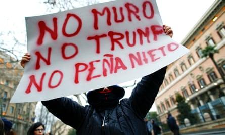 A demonstrator holds a placard saying: 'No wall, no Trump, no Peña Nieto.'
