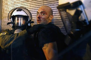 A protester is arrested by riot police following clashes in Athens. Anti-establishment demonstrators threw petrol bombs at police in front of parliament ahead of the key vote on a bailout deal. Police responded with teargas, sending hundreds of people fleeing in central Syntagma Square.