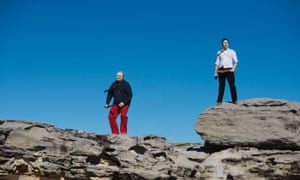 Two men standing on rocks in corporate-wear, with painted faces