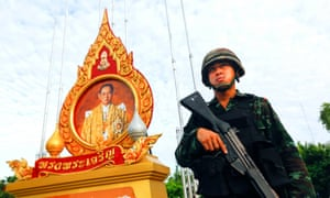 A soldier stands guard beneath a portrait of King Bhumibol Adulyadej outside Government House in Bangkok, Thailand.