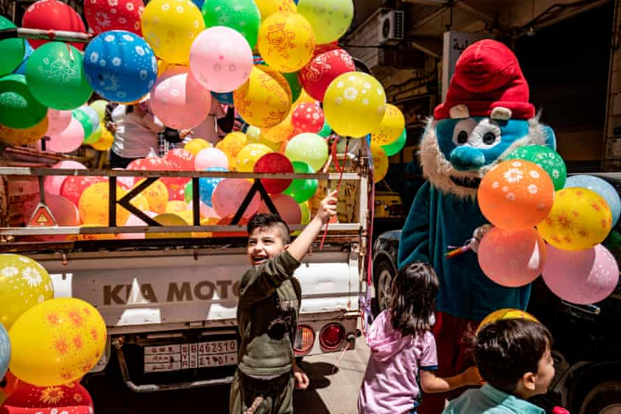 A mascot dressed as a Smurf hands balloons to children as part of a local NGO awareness campaign to encourage hand-washing, hygiene, and social distancing in response to the pandemic in Qamishli, Syria.