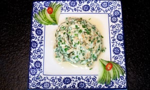 A square blue floral plate with a mound of herb-flecked scrambled egg and decorative cucumber slices in two corners