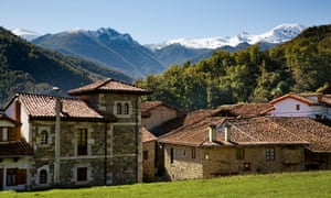 The village of Mogrovejo, in northern Spain, in bright sunshine, with the peaks of the Picos de Europa in the background.