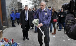 New York City police commissioner Bill Bratton leaves flowers at an impromptu memorial.