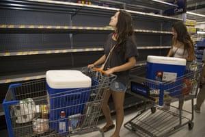 Young women look at empty shelves in a Walmart in Honolulu