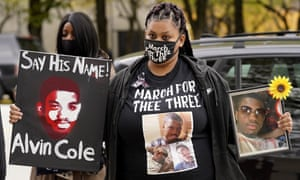 Tristiana Cole holds a sign and a photo of her brother Alvin Cole as she arrives for a Get Out The Vote rally in Chicago in October.