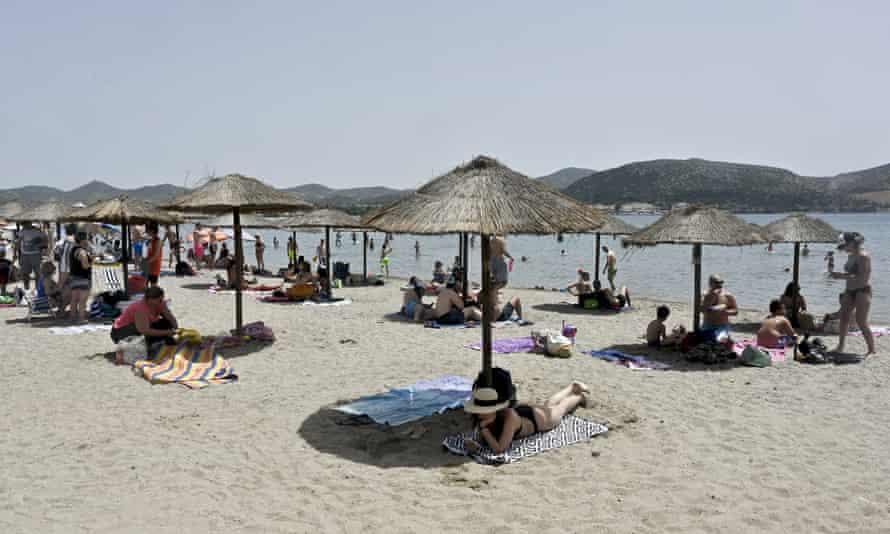 People enjoying the sea and sun at Anavisos beach near Athens on Saturday