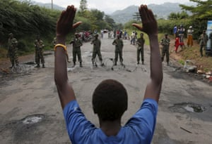Protester in Bujumbura holds his hands up in front of soldiers during a protest against President Nkurunziza and his bid for a third term