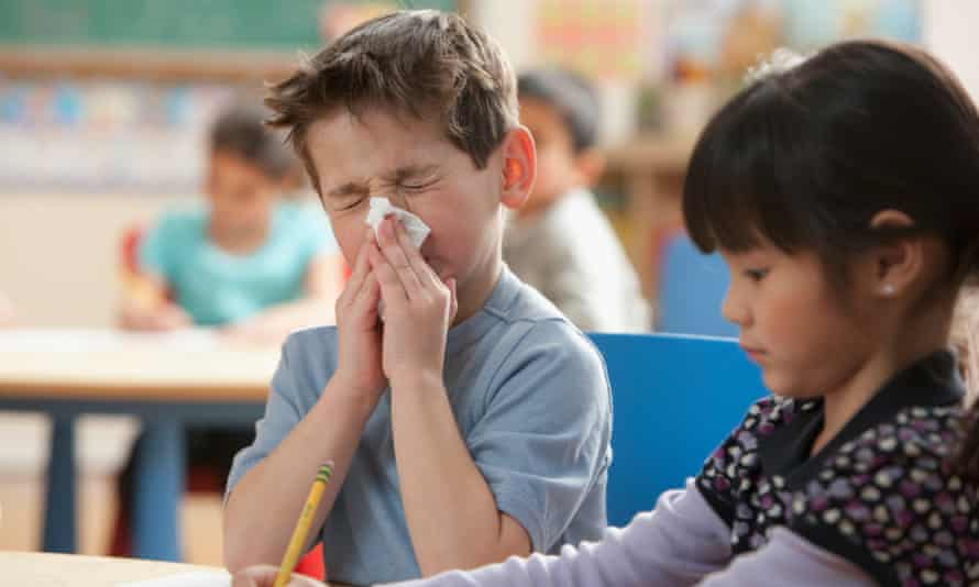 boy blowing nose in classroom