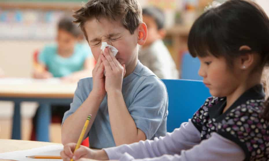 Boy blowing his nose in a classroom