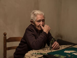 Maria Novela, 85, plays cards with her husband at their home in Selas.