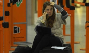 A woman in a queue at the airport, sitting on her suitcase, talking on the phone