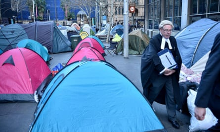 A barrister walks between tents set up in Martin Place where homeless people have set up camp in the central business district of Sydney.